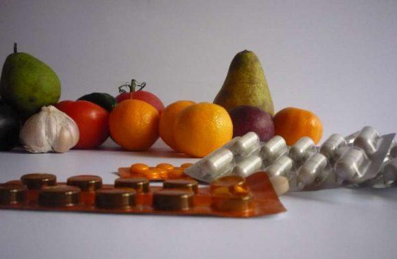Birnen, Mandarinen, Tomaten und Knoblauchhinter Tablettenpackungen